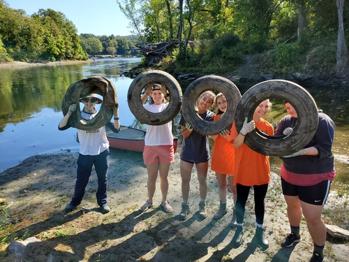 Volunteers hold tires cleaned out of the river basin.
