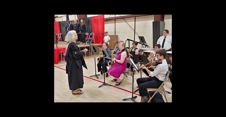 Retiring music teacher Karen Horton conducts the band during graduation.