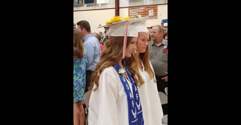 Seniors Grace Russell and Kendell Howe march out of the gym.