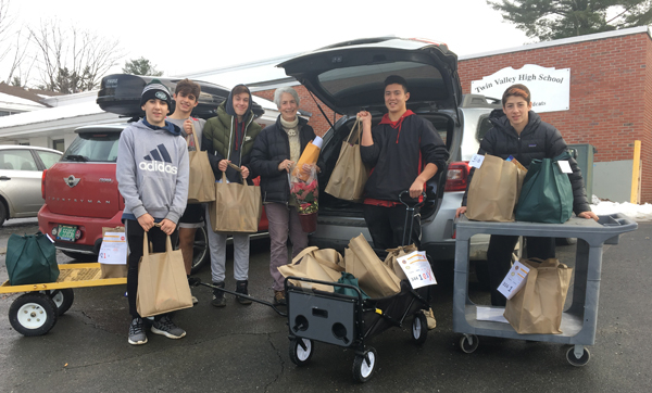 Twin Valley students Aaron Soskin, Casey Sibilia, Owen Grinold, Izaak Park, and Lucas Messing help load volunteer Karen Hein's car with bags of food and poinsettia plants  all destined for Whitingham families.