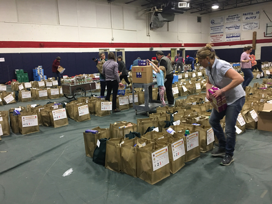 """A beehive of packing activity involved dozens of volunteers coming together to help with the """"food insecurity"""" problem."""