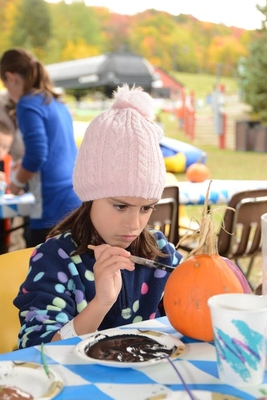 Pumpkin painting and face painting are offered in the kid zone.