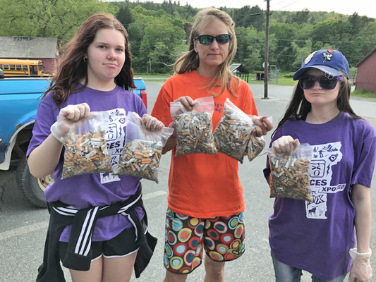 Sawyer King, Jen Nilsen, and Catherine Thomas clean up cigarettes along Route 9.