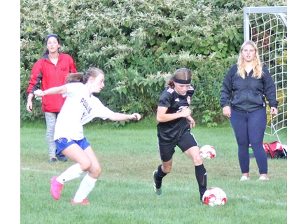 Twin Valley's Reese Croutworst motors by Poultney's Bella Mack while coaches Taryn Lawrence, left, and Kara Bird look on. Randy Capitani
