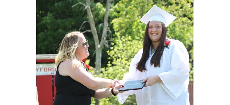 Twin Valley principal Anna Roth congratulates senior Leora Longe during graduation ceremonies Saturday at Hayford Field in Wilmington.                                                                                                                    Tyler Lederer